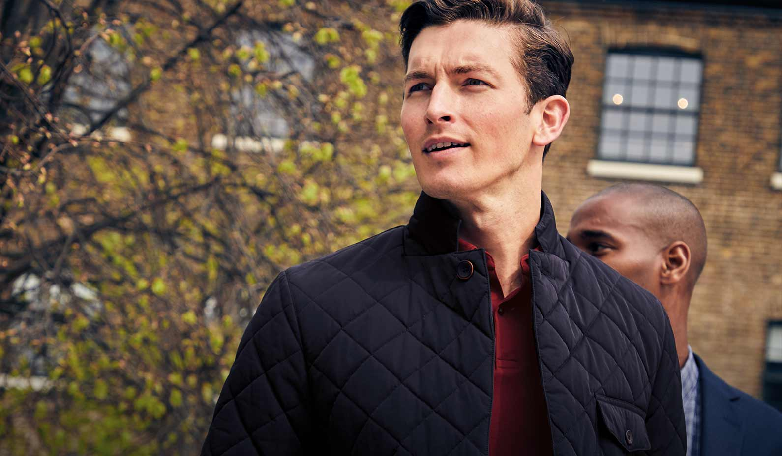 Man in navy quilted jacket and burgundy jersey
