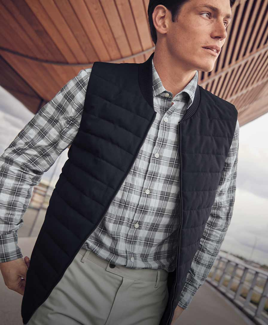 A man wearing check shirt a gilet