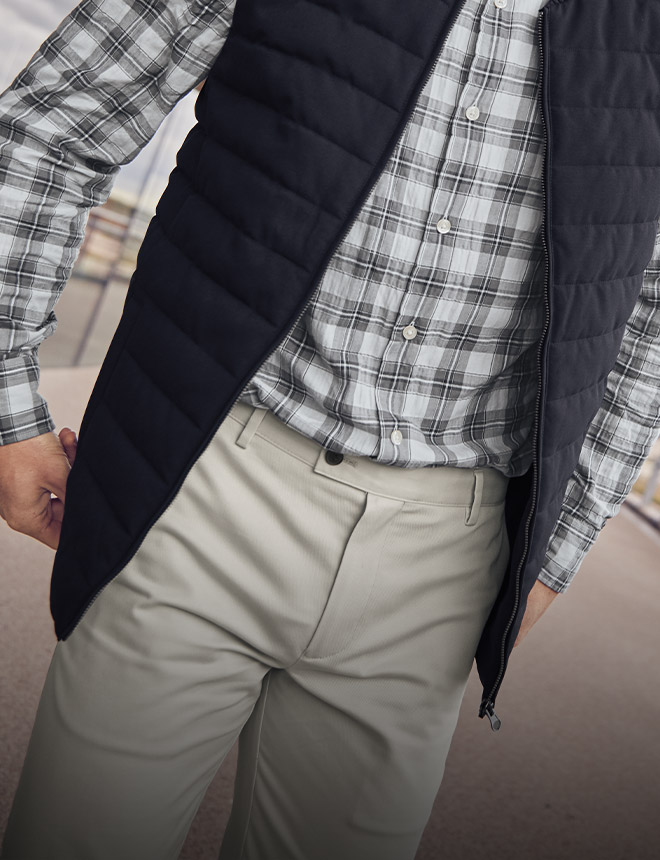 man in natural colour ultimate chinos with checked casual shirt and navy gilet