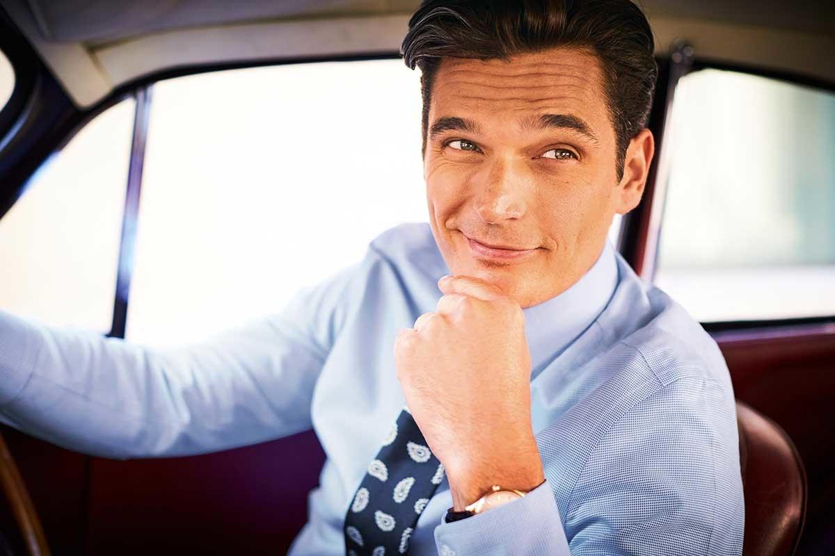 model draagt een strijkvrij overhemd met een blauwe stropdas