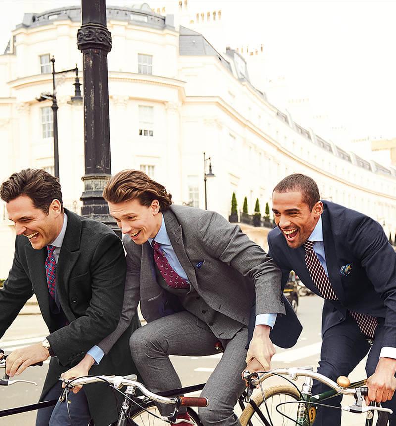 4 men in suites riding bikes