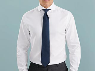 Man in white shirt with plain navy tie