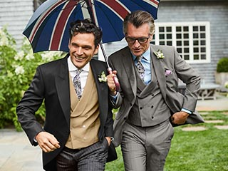Two men in morning suits holding a union jack umbrella
