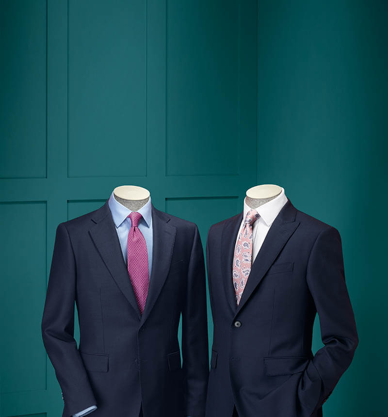 2 mannequins wearing suits with green background