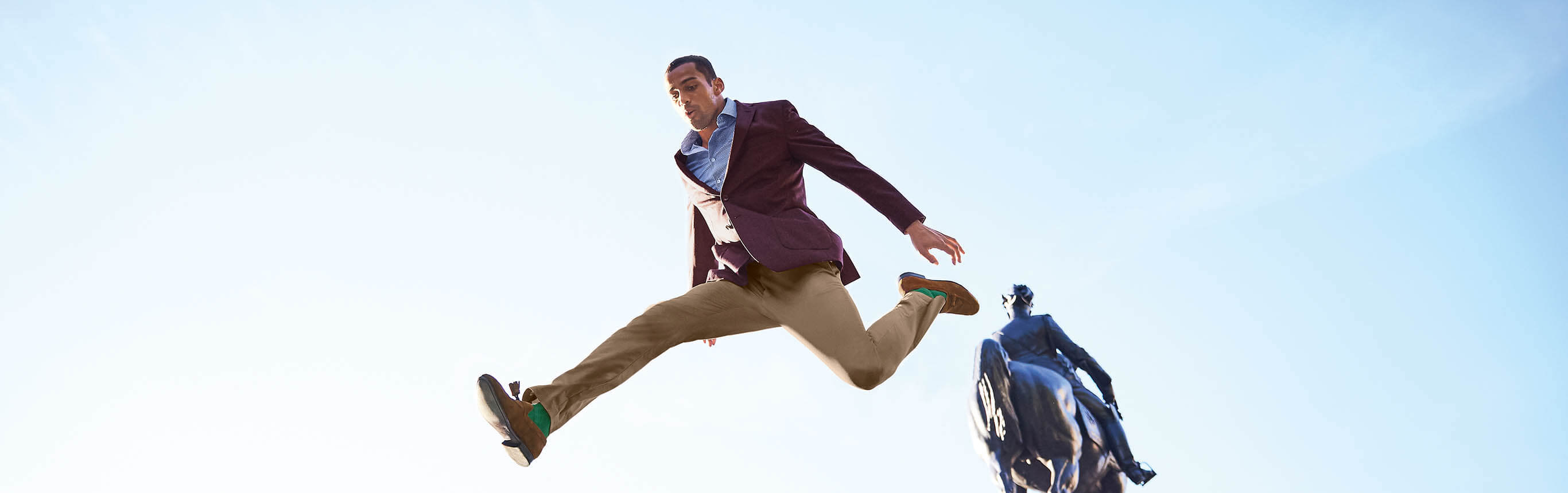 A man in a suit jumping in the air