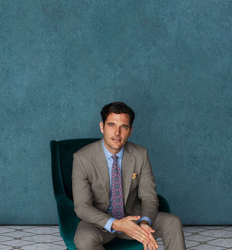 man wearing a suit sitting  on a chair with green background