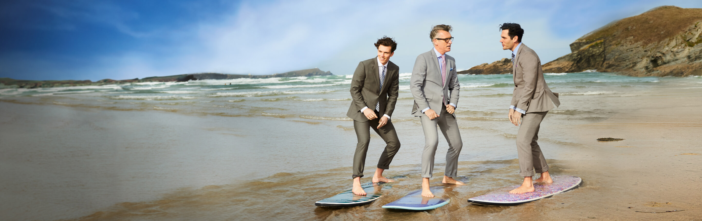 3 men in suits on surfboards